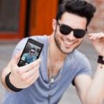 unga manliga modellen att göra självporträtt med en smartphone — Stockfoto