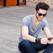 Attractive young male model texting on a smartphone — Stock Photo #21437887