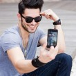 图库照片: Young male model photographing himself with smartphone