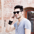 Handsome young man talking on a smartphone — Stock Photo
