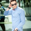 Attractive young male model posing outdoors in blue shirt and sunglasses — Stock Photo
