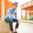 Handsome young male model posing outdoors in blue shirt and sunglasses — Stock Photo