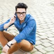 Handsome young man talking on a smartphone outdoors — Stock Photo #21438847