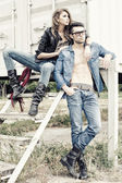 Stylish couple wearing jeans and boots posing dramatic - retro processed image — Стоковое фото