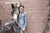 Sexy and fashionable couple wearing jeans, shoot in a grungy location - landscape orientation with copy-space — Foto Stock