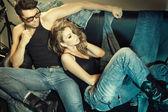 Sexig man och kvinna klädd i jeans gör ett mode foto skjuta i en professionell studio — Stockfoto