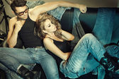 Sexy man and woman dressed in jeans doing a fashion photo shoot in a professional studio — Zdjęcie stockowe