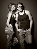Sexy man and woman doing a fashion photo shoot in a professional studio — Stock Photo