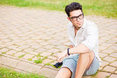 Handsome man wearing glasses sitting on the sidewalk looking awa — Stock Photo