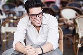 привлекательный мужчина в очках, стоя на террасе смеется — Стоковое фото