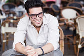 Attractive man wearing glasses standing at a terrace laughing — Stok fotoğraf