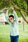 Handsome man wearing sunglasses relaxing in the park — Stock Photo