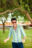 Handsome man wearing sunglasses having fun in the park — Stock Photo