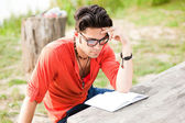 Student wearing glasses reading in the park — Stock Photo