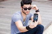 Young male model making self portrait with a smartphone — Stock Photo