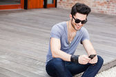 Attractive young male model texting on a smartphone — Stock Photo