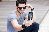 Young male model photographing himself with a smartphone — Stock Photo