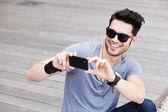 ελκυστική ανδρικό πρότυπο, λήψη των φωτογραφιών με ένα μαύρο smartphone — Φωτογραφία Αρχείου