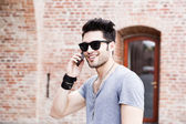 Handsome young man talking on a smartphone — Stok fotoğraf