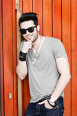 Sexy man posing outdoors with sunglasses — Stock Photo