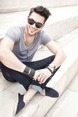 Moda hombre guapo modelo sonriente, vestido casual - al aire libre — Foto de Stock