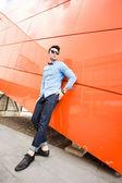 Hübscher junge männliches model posiert im freien im blauen hemd und sonnenbrille — Stockfoto