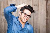 Knappe jonge man die lacht buitenshuis — Stockfoto