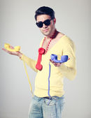 Handsomen and funny guy with hipster glasses and colouful phones — Stock Photo