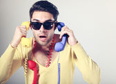 Funny call center guy with hipster glasses and colouful phones — Stock Photo