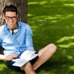 ler man med en bok på gräset i parken — Stockfoto