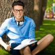 Smiling man holding a book on the grass in the park — Stock Photo