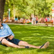 Handsome man writing something and relaxing on the grass in the — Stock Photo