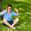 Stock Photo: Handsome msmiling and listening to music on grass in the