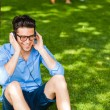 Handsome man smiling and listening to music on the grass in the — Stock Photo