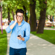 Handsome man smiling and listening to music in the park — Stock Photo