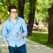 Handsome man smiling and listening to music in the park — Stock Photo #21440847