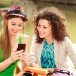 Stock Photo: Two beautiful women playing on smart-phone and chatting on river side terrace
