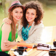 Two beautiful women drinking coffee and smiling on the river sid — Stock Photo