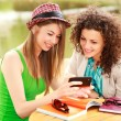 Two beautiful women playing on a smart-phone and chatting on the river side terrace — Stock Photo #21445437