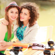 Two beautiful women drinking coffee and smiling on the river side terrace — Stock Photo #21445439