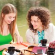 Stock Photo: Two beautiful women chatting over coffee at river side terrace