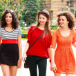 Three beautiful women walking and smiling on the street - sunny day — Stock Photo