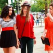 Three beautiful women walking and smiling on the street - sunny day - Stock Photo