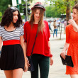 Three beautiful women walking and smiling on the street - sunny day - Стоковая фотография
