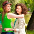 Two beautiful women walking and smiling in the park by the river - sunny day - Stock Photo