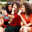 Foto Stock: Three beautiful women photographing themselves eating icecream