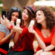 Three beautiful women photographing themselves eating icecream — Stock Photo