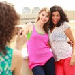 Three beautiful women photographing themselves - Stock Photo