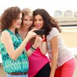 Three beautiful women looking on a smartphone — Stock Photo #21447257