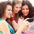 Foto Stock: Three beautiful women looking on smartphone